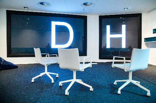 Three white chairs and two large screens bearing the letters DH